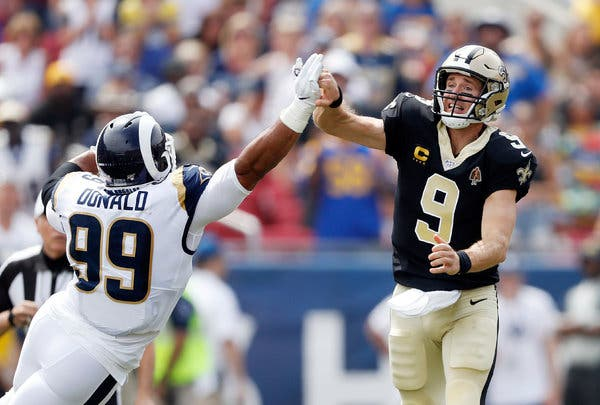 Drew Brees throws ball to receiver and jams thumb into Aaron Donald's Hand.  Photo Courtesy of: The New York Times