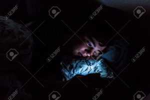 A teenager looking on his phone at night before he goes to bed. (Photo Courtesy of 123RF)