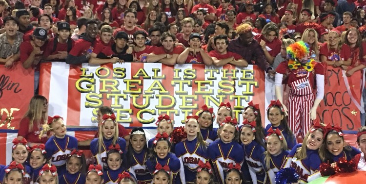 Students at the game pose in front of a student section sign.